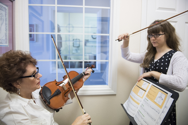 Sixty-two-year-old Martha Kilcoyne, left, is taught how to play the violin by music instructor Stacy Honaker at the Brill Music Academy in Las Vegas on Saturday, March 14, 2015. (Martin S. Fuentes ...