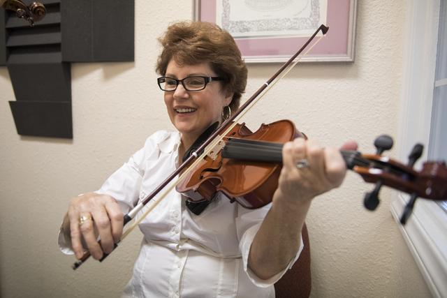 Sixty-two-year-old Martha Kilcoyne learns how to play the violin by music instructor Stacy Honaker (not shown) at the Brill Music Academy in Las Vegas on Saturday, March 14, 2015. (Martin S. Fuent ...