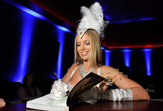 "Author, model and naughty lifestyle expert Sienna Sinclaire signs her new book, ""Naughty Girl's Guide to Las Vegas,"" at Sapphire Gentlemen's Club in Las Vegas on Friday, Feb. 20, 2015. ( ..."