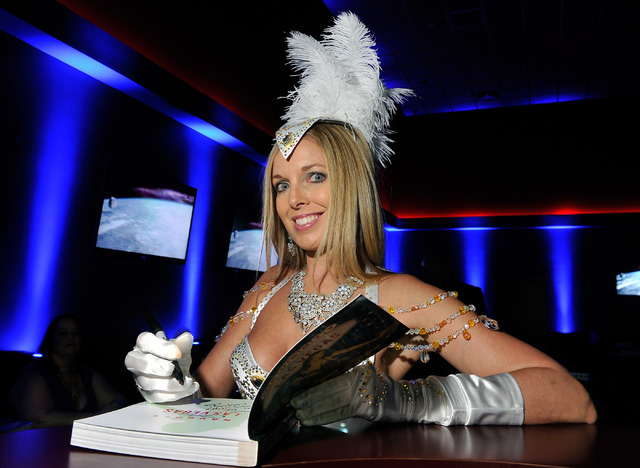 """Author, model and naughty lifestyle expert Sienna Sinclaire signs her new book, """"Naughty Girl's Guide to Las Vegas,"""" at Sapphire Gentlemen's Club in Las Vegas on Friday, Feb. 20, 2015. (David Beck ..."""