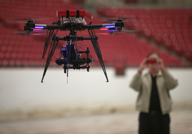 Ron Futrell takes photos of an Unmanned Aerial Vehicle that is made up of a drone and a gimbal camera as it flies through the air during a test run at South Point Wednesday, Feb. 25, 2015, in Las  ...