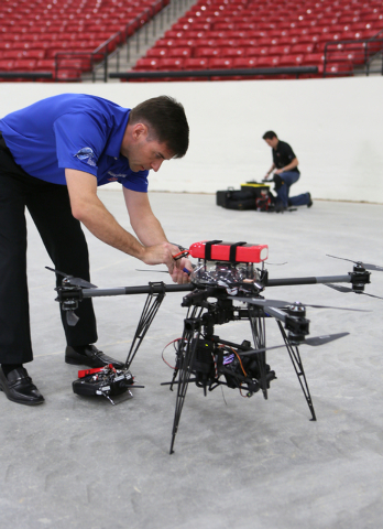 Bill Wilson, front, and Jason Daub work on an Unmanned Aerial Vehicle that is made up of a drone and a gimbal camera before it flies during a test run at South Point Wednesday, Feb. 25, 2015, in L ...