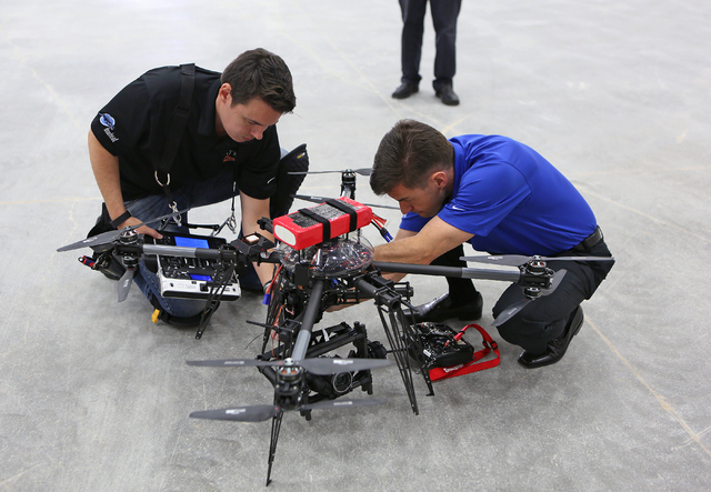 Jason Daub, left, and Bill Wilson work on an Unmanned Aerial Vehicle that is made up of a drone and a gimbal camera before it flies during a test run at South Point Wednesday, Feb. 25, 2015, in La ...