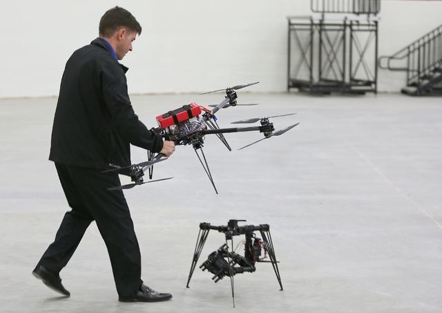 Bill Wilson carries a drone, the upper part of an Unmanned Aerial Vehicle, which he will connect to a gimbal camera, on the ground, before it flies during a test run at South Point Wednesday, Feb. ...