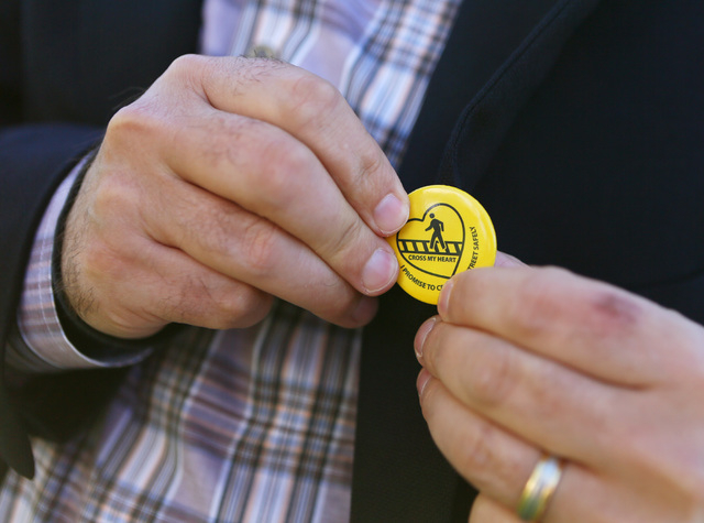 Kyle Kubovchik puts on pin at the start of a news conference on pedestrian safety efforts Thursday, March 5, 2015, in Henderson. Regional Transportation Commission and Nevada Department of Transpo ...