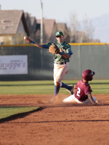 Green Valley High School Sophomore A.J. Amelburu(4) throws towards first base after getting Desert Oasis High School Senior Chris Van Kuren(2) during the Lions Kick Off baseball tournament, Champi ...