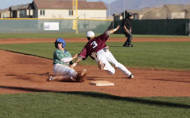 Green Valley High School Sophomore A.J. Amelburu(4) slides into third base and is tagged by Desert Oasis High School Senior Caeden Marin(3)  during the Lions Kick Off baseball tournament, Champion ...
