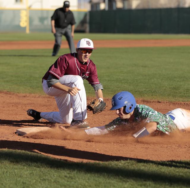 Green Valley High School Sophomore A.J. Amelburu(4) slides back towards third base after being caught between home and third base but is called safe after  Desert Oasis High School Senior Caeden M ...