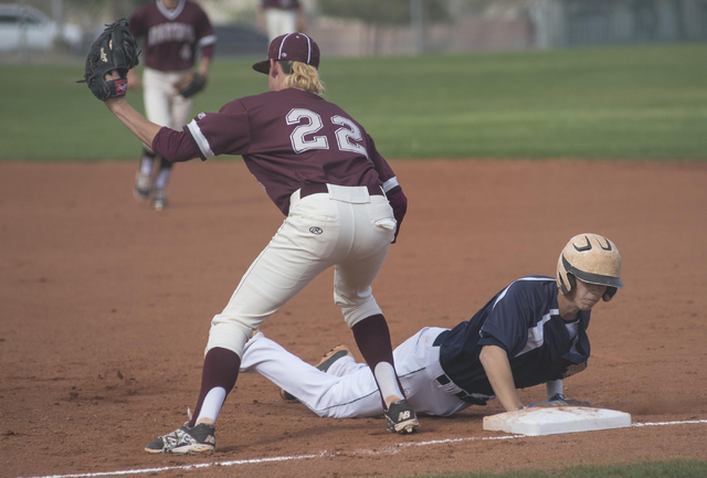 Cimarron-Memorial High School's Larry Quaney (22), catches a pickoff attempt as  Shadow Ridge High School's Trevin Reynolds (19) dives back to first on Thursday, Feb. 12, 2015, at Cimarron-Memoria ...
