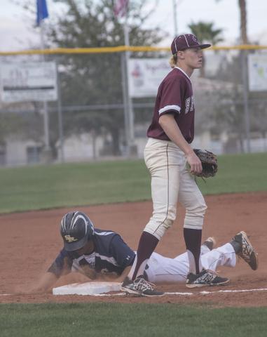 Cimarron-Memorial High School's Trevor Lippard (12), waits for the ball as Shadow Ridge High School's Eric Jordan (21) slides into third base on Thursday, Feb. 12, 2015, at Cimarron-Memorial in La ...