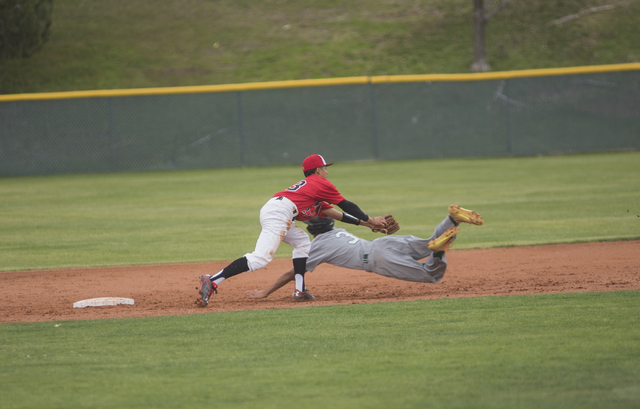 Rancho High School's David Arambula (3) slides into second base as Las Vegas High School's Andrew Aleman (23) attempt to tag him out during their baseball game played at the Las Vegas High School  ...