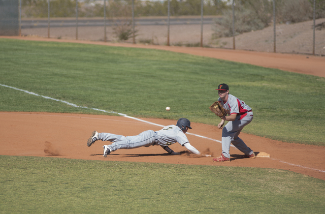Boulder City's Zach Murphy (3) slides back to first before being tagged by Tech's Logan Campbell (34) during their baseball game played at the Burkholder Park baseball field in Henderson, Nev., on ...
