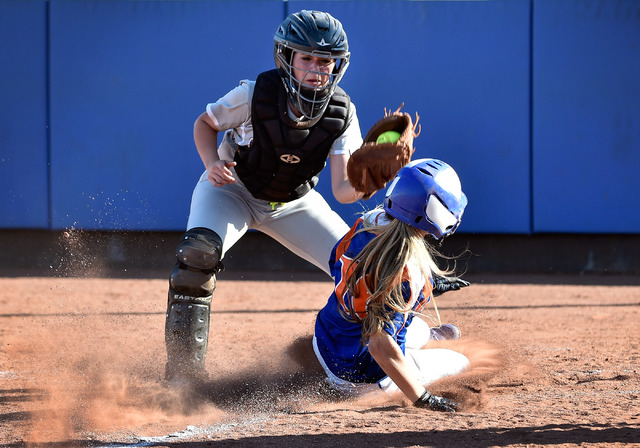 Bishop Gorman's Ashley Witucki beats the tag by Faith Lutheran catcher Claire Peck as she slides home during a high school softball game at Bishop Gorman High School on Monday, March 9, 2015, in L ...