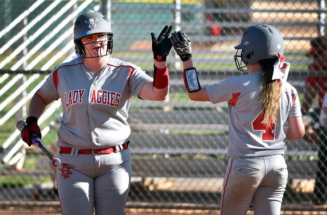 Arbor View's Marissa Bachman gets a high-five from Breanne Henricksen (4) after Bachman scored a run during a high school softball game against Liberty at Liberty High School on Tuesday, March 24, ...