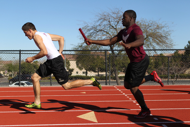 Faith Lutheran runner Mark Rubalcaba, 18, left, works on the baton pass with teammate Alfred Soboyejo IV during a track practice at Faith Lutheran High School in Las Vegas Monday, March 9, 2015. R ...