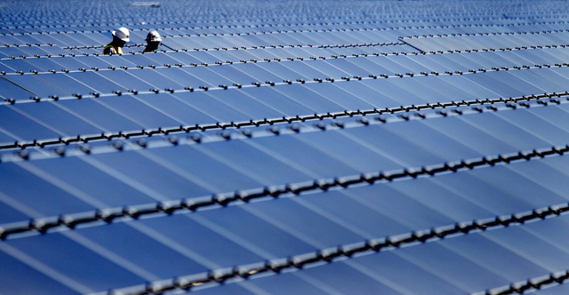 JEFF SCHEID/LAS VEGAS REVIEW-JOURNAL Two men walk through solar panels at the Silver Star North Solar Project in Ivanpah Valley on Tuesday, Sept. 20, 2011. The 50 megawat photovoltaic facility, bu ...