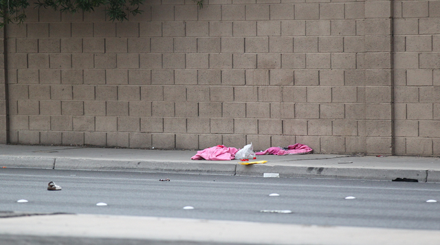 Personal belongings are seen as Las Vegas police investigate where a woman was struck by a car on Rainbow Boulevard near Twain Avenue on Wednesday, March 11, 2015. The woman, believed to be in her ...