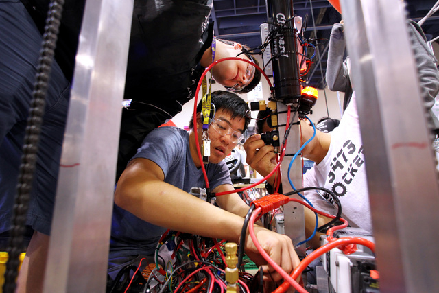 Jonathan Khodr, top, Brandon Hung and Hall Chin, partially hidden, from Diamond Bar (California) High School, make adjustments to their robot in the pit area during practice for the FIRST Robotics ...