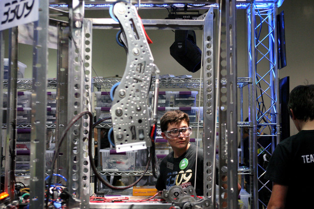 Nick Capdevila of Anaheim, Calif., makes last-minute checks on Team 3309's robot for the Recycle Rush challenge in the FIRST Robotics Competition at Cashman Center in Las Vegas on Thursday, March  ...