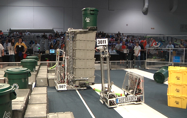 The Highrollers robotics team, entry #987, from Cimarron-Memorial High School in Las Vegas, score high points with a seven-container stack in the Recycle Rush challenge at the FIRST Robotics Compe ...