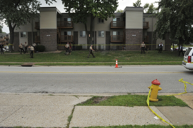 Police officers investigate at the scene of the August 9 Ferguson Police shooting of Michael Brown in Ferguson, Missouri in this handout evidence photo released by the St. Louis County Prosecutor' ...