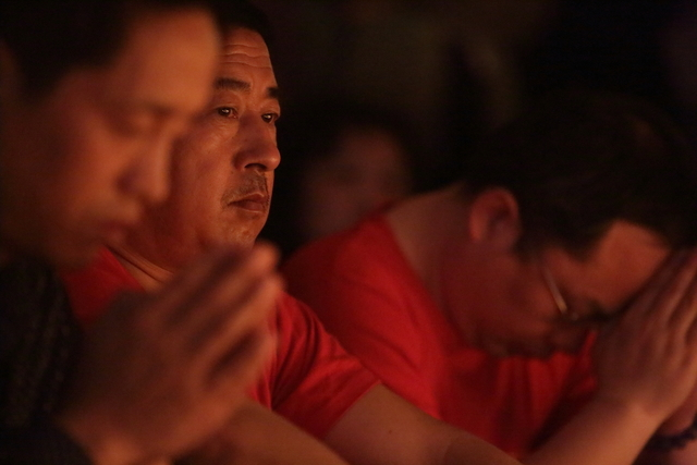 Families of the MH370 passengers hold a candlelight vigil in Beijing, China on Tuesday, April 8, 2014. They wait in hope for any news on their loved ones one month to the day after MH370 went missing.