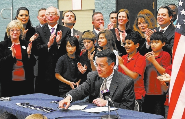 A crowd of lawmakers and fifth-graders applaud after Gov. Brian Sandoval signs the school bond bill into law at a local elementary school in Carson City, Nev., on Wednesday, March 4, 2015. The bil ...