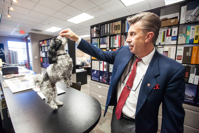 Ed Vance gives a treat to his dog Pepper, a 7-year-old Shih Tzu, at architecture firm Ed Vance & Associates Architects, 900 S. Pavilion Center Drive, Suite 180, Feb. 27, 2015. Vance has been regul ...