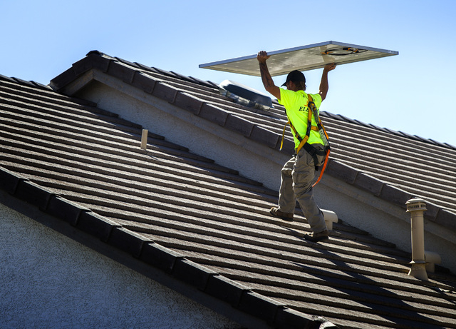Jacy Sparkman with  Robco Electric carries a solar panel at a home in northwest Las Vegas on Friday March 13, 2015. The company estimated that the 17 panel  4.675 KWDC solar project will save this ...
