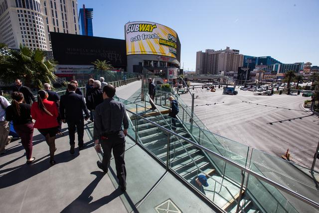 People walk along a pedestrian bridge over Las Vegas Boulevard at Harmon Avenue in Las Vegas on Wednesday, March 4, 2015. (Chase Stevens/Las Vegas Review-Journal)