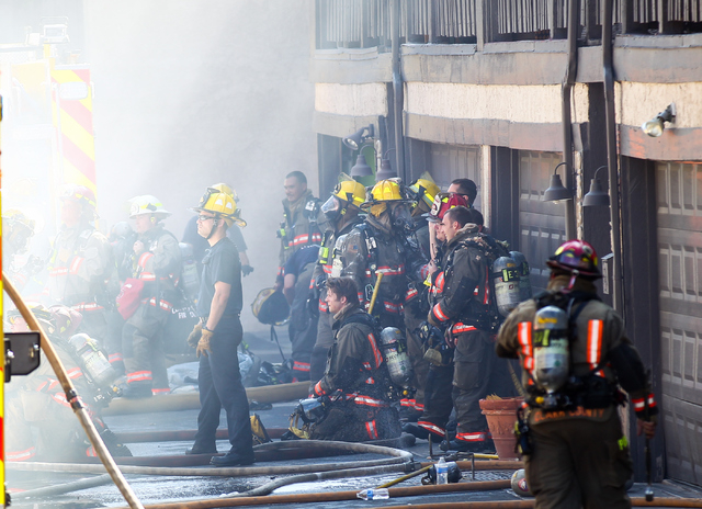 Clark County firefighters stand and sit for a moment while responding to an apartment fire off of Tropicana Avenue near McLeod Drive in Las Vegas on March 30, 2015. (Chase Stevens/Las Vegas Review ...