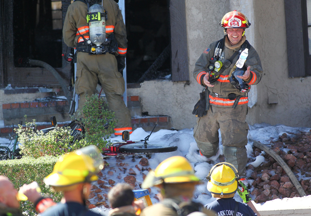 A Clark County firefighter reaches to catch a bottled water after an apartment fire is extinguished at Tropicana Avenue near McLeod Drive in Las Vegas on March 30, 2015. (Chase Stevens/Las Vegas R ...