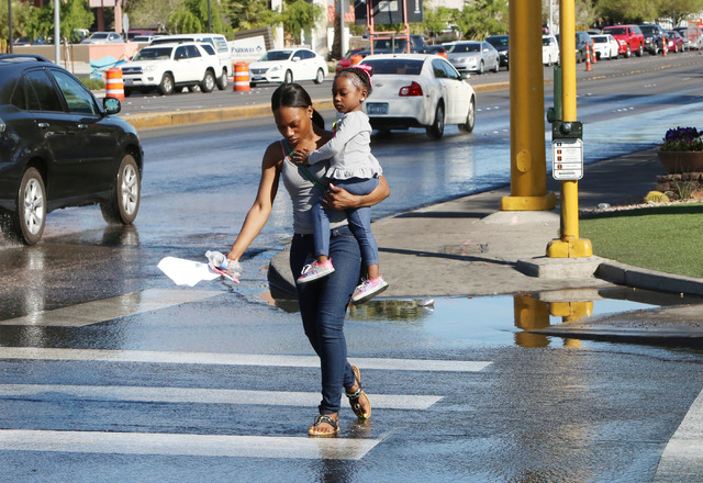 Simone Howard and her 3-year-old daughter, Samya, navigate through the flooded street, due to water main break, at Desert Inn Road and Maryland Parkway on Thursday, March 26, 2015. Crews are tryin ...