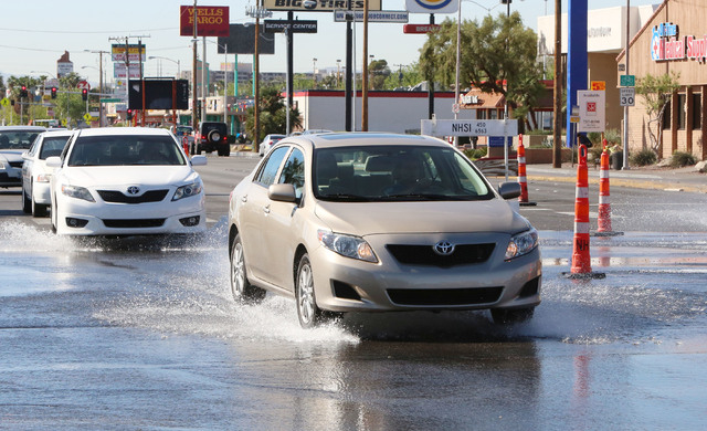 Cars navigate through flooded street due to water main break at Desert Inn Road and Maryland Parkway on Thursday, March 26, 2015. Crews are trying to replace a leaking valve but have to wait until ...
