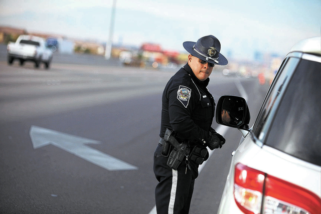 Trooper Loy Hixson of the Nevada Highway Patrol speaks with a man he pulled over for speeding along Interstate 15 south of Las Vegas Saturday, Jan. 11, 2014. (John Locher/Las Vegas Review-Journal)