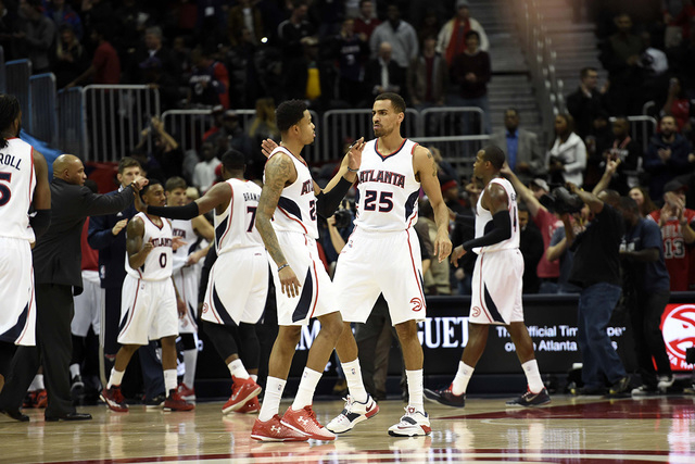 Dec 15, 2014; Atlanta, GA, USA; Atlanta Hawks guard Kent Bazemore (24) and guard Thabo Sefolosha (25) react of the bench after defeating the Chicago Bulls at Philips Arena. The Hawks defeated the  ...