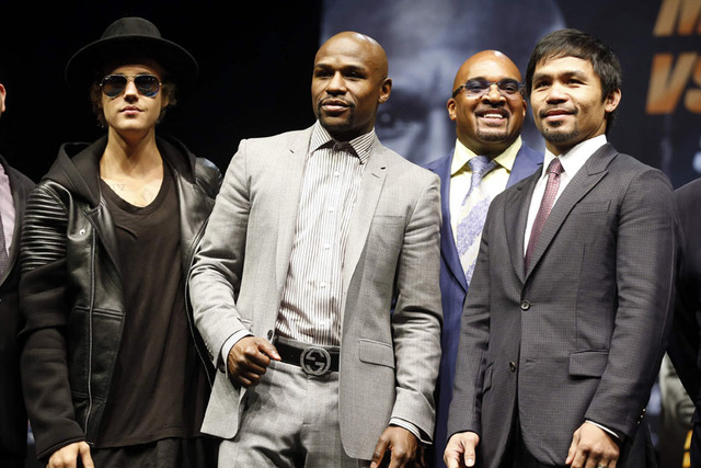 """Eleven-time, five-division world boxing champion Floyd """"Money"""" Mayweather (2nd L) and eight-division world champion Manny """"Pac-Man"""" Pacquiao (R) pose with Justin Bieber (L) at a news conference, a ..."""