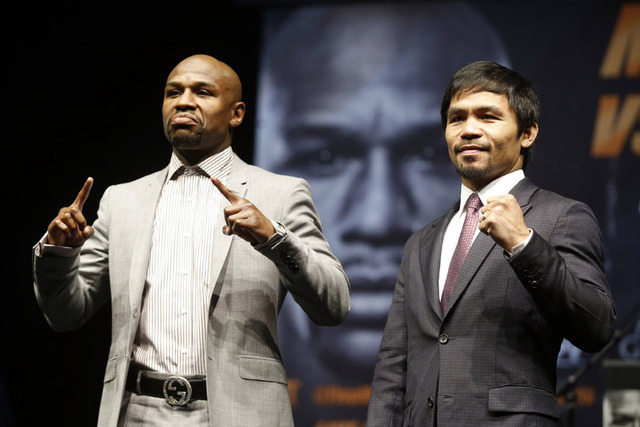 """Eleven-time, five-division world boxing champion Floyd """"Money"""" Mayweather (L) and eight-division world champion Manny """"Pac-Man"""" Pacquiao pose at a news conference ahead of their upcoming bout, in  ..."""