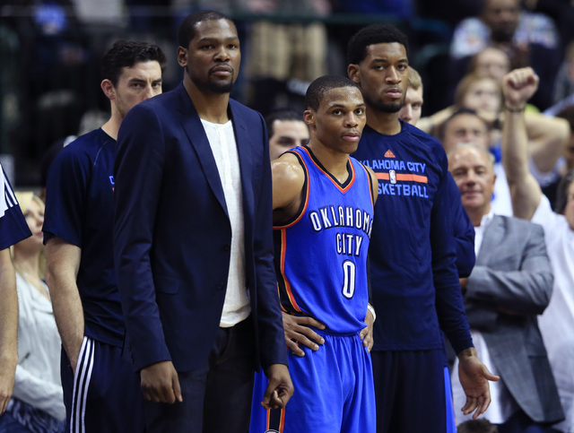 Mar 16, 2015; Dallas, TX, USA; Oklahoma City Thunder forward Kevin Durant (left) and guard Russell Westbrook (0) and forward Perry Jones (right) react on the bench during the second half against t ...