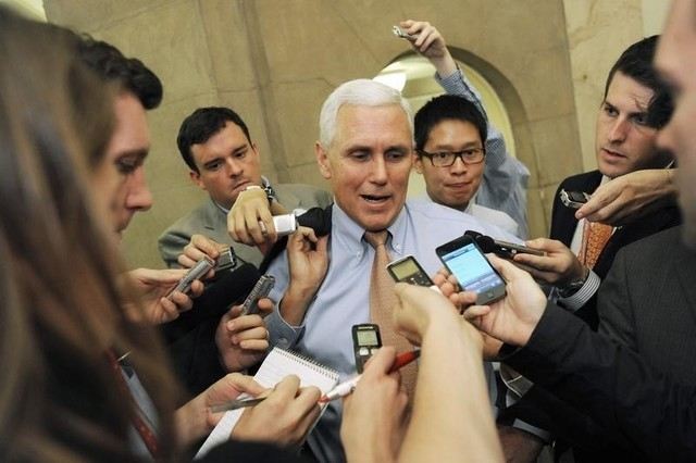 Mike Pence talks with reporters as he departs a meeting at the U.S. Capitol in Washington, July 28, 2011. On Tuesday, Pence asked lawmakers to fix a previously enacted measure to avoid any discrim ...
