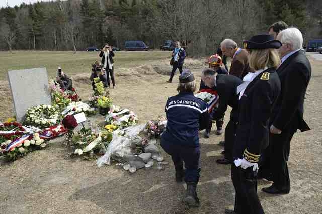 French Interior Minister Bernard Cazeneuve (2ndL) is helped by a gendarme as he places a wreath by a stele in memory of the victims of the Germanwings Airbus A320 crash, on April 3, 2015  in the v ...