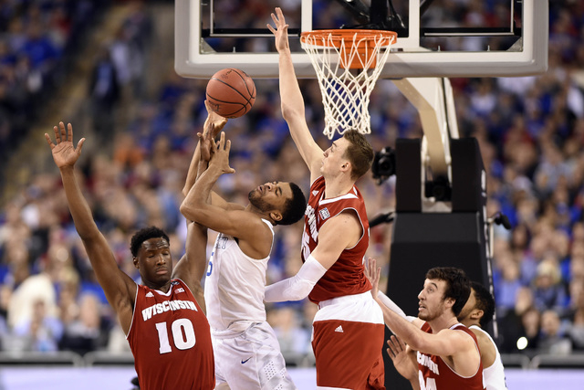 Apr 4, 2015; Indianapolis, IN, USA; Kentucky Wildcats guard Andrew Harrison (5) is defended by Wisconsin Badgers forward Nigel Hayes (10) and forward Frank Kaminsky (44) and forward Sam Dekker (15 ...
