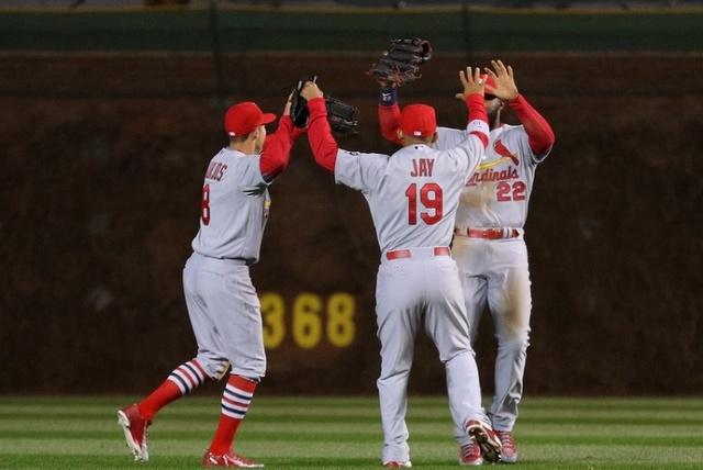 Apr 5, 2015; Chicago, IL, USA; St. Louis Cardinals left fielder Peter Bourjos (left ) and center fielder Jon Jay (center) and right fielder Jason Heyward (right) celebrate their victory following  ...