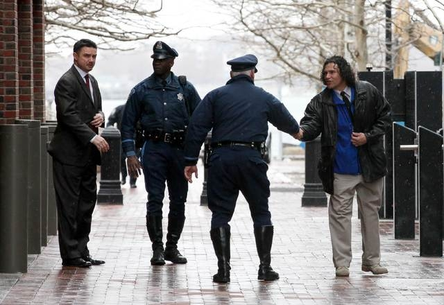 Carlos Arrendono (R), who was on scene helping the injured after the Boston marathon bombing, shakes hands with a police officer after a jury found Boston Marathon bombing suspect Dzhokhar Tsarnae ...