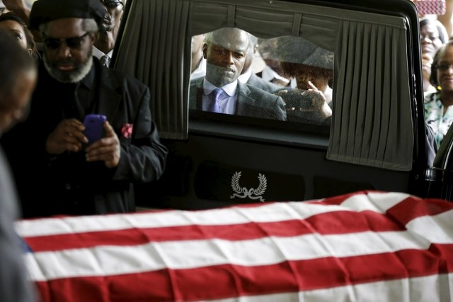 Mourners, and ABC News correspondent Kendis Gibson (C), look on as the casket of Walter Scott is removed from a hearse for his funeral at W.O.R.D. Ministries Christian Center, Saturday, April 11,  ...