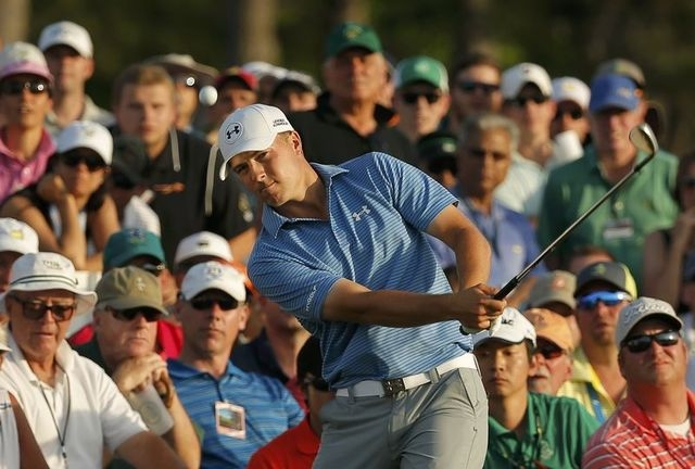 Jordan Spieth of the U.S. chips onto the 18th green from the gallery during third round play of the Masters golf tournament at the Augusta National Golf Course in Augusta, Georgia, April 11, 2015. ...