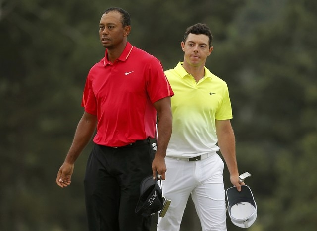 Tiger Woods of the U.S. (L) and Rory McIlroy of Northern Ireland finish their round on the 18th green during the final round of the Masters golf tournament at the Augusta National Golf Course in A ...