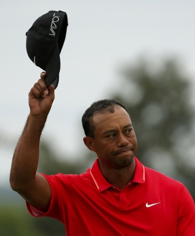 Tiger Woods of the U.S. waves to the crowd as he walks off the 18th green during the final round of the Masters golf tournament at the Augusta National Golf Course in Augusta, Georgia April 12, 20 ...