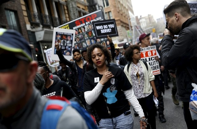 Demonstrators protest against police brutality against minorities during a protest in New York, April 14, 2015. Protestors angered by fresh cases of police violence against unarmed black men in th ...