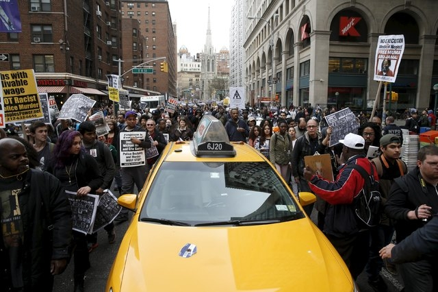 Demonstrators march past a taxi during a protest against police brutality against minorities in New York, April 14, 2015. Protestors angered by fresh cases of police violence against unarmed black ...